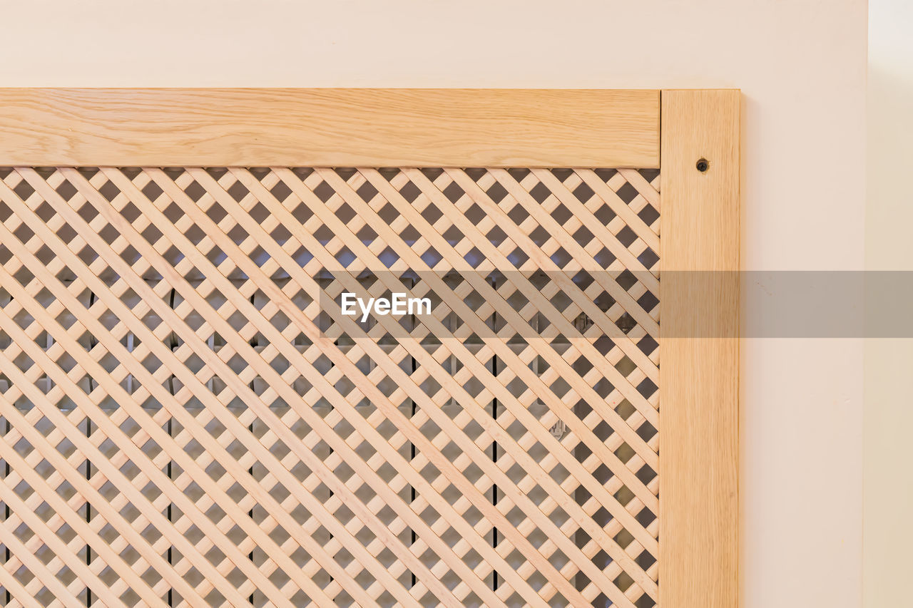Close-up of wooden heater decorative panel against wall at home