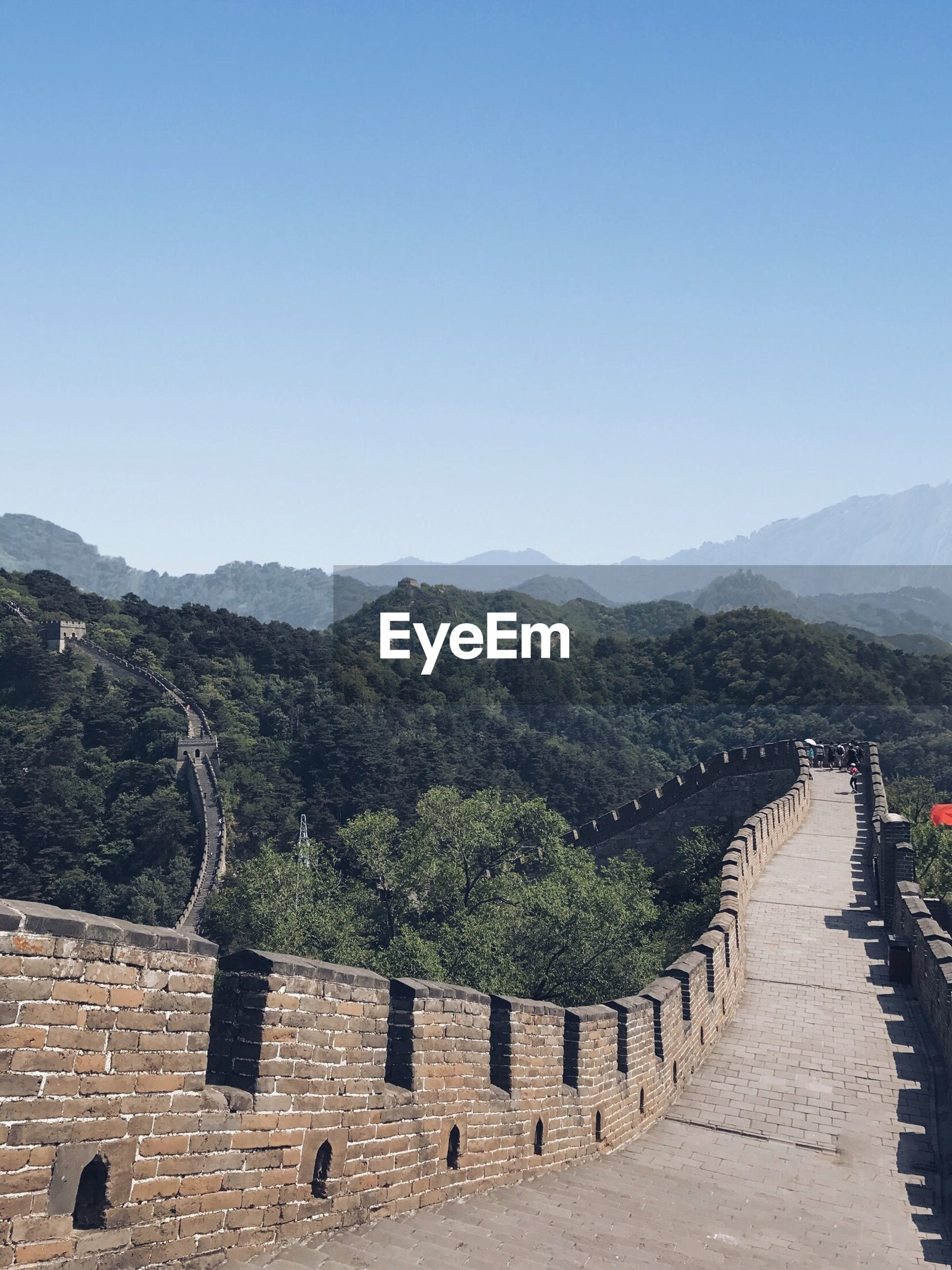 Great wall of china leading towards mountains against clear sky