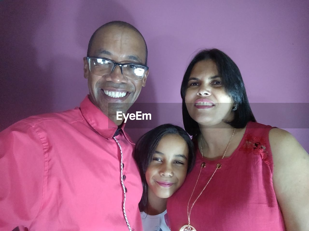 Portrait Of Smiling Family Standing Against Wall