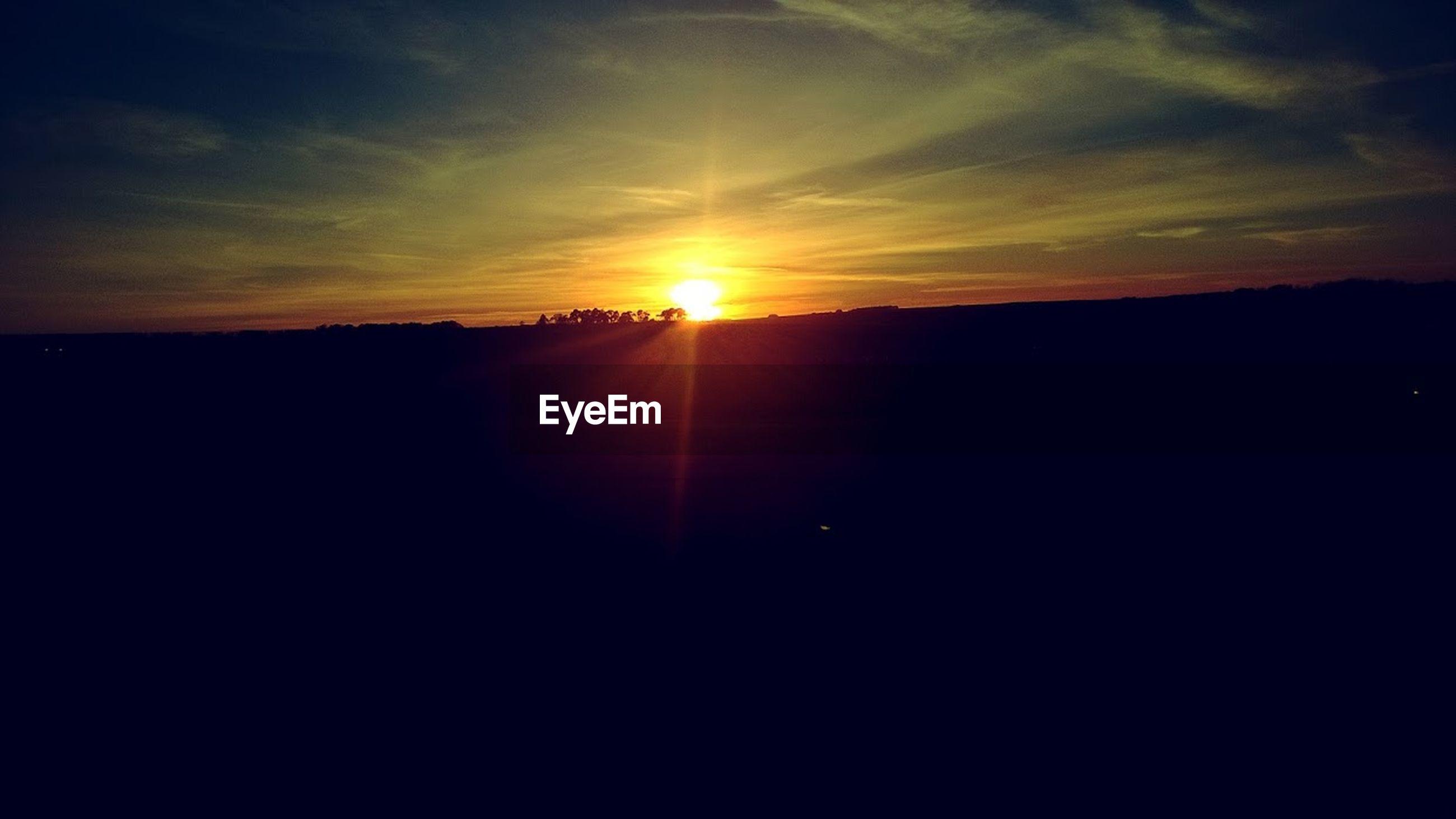 sky, sunset, sun, sunlight, beauty in nature, scenics - nature, tranquility, nature, cloud - sky, sunbeam, silhouette, orange color, environment, lens flare, tranquil scene, landscape, idyllic, no people, outdoors, horizon, dark, bright