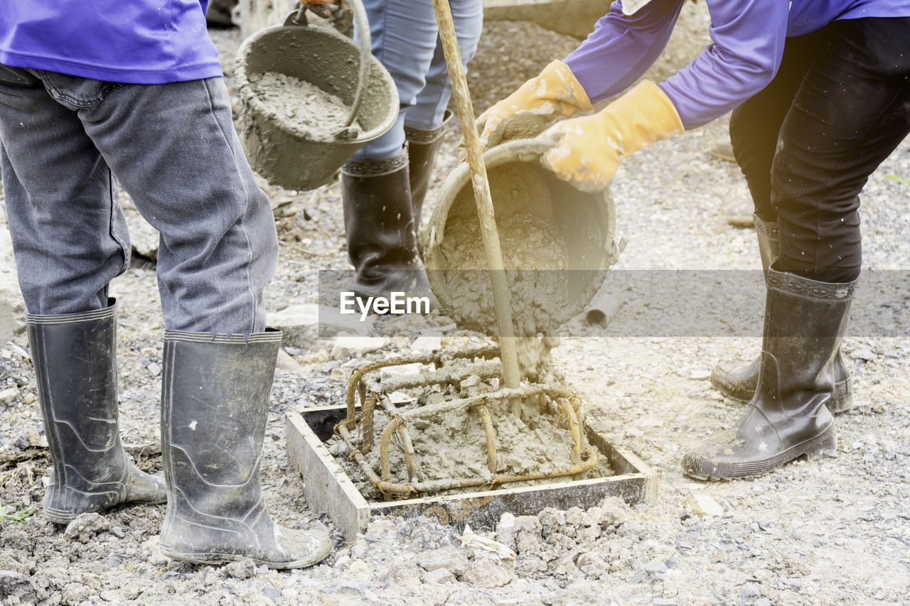 working, occupation, cooperation, teamwork, men, people, real people, water, motion, industry, construction industry, day, outdoors, nature, standing, low section, adult, coworker, rubber boot