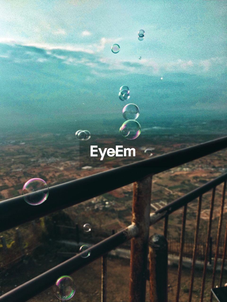 Close-Up Of Bubbles On Railing Against Landscape