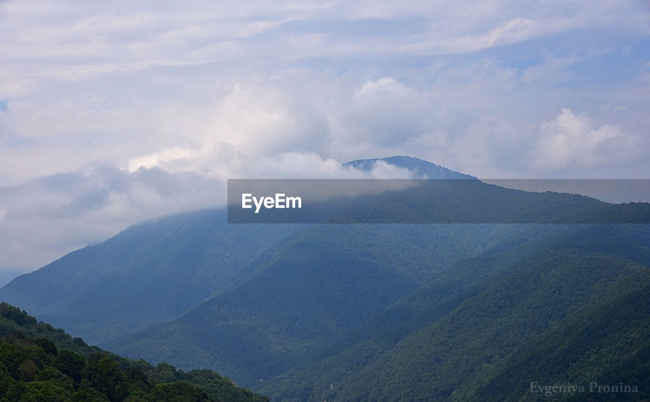 beauty in nature, cloud - sky, scenics - nature, mountain, tranquil scene, sky, tranquility, non-urban scene, environment, landscape, mountain range, nature, no people, day, idyllic, tree, remote, outdoors, physical geography, mountain peak, range