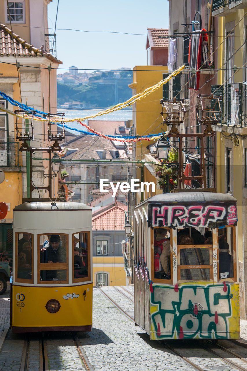 architecture, city, building exterior, built structure, transportation, yellow, mode of transportation, day, public transportation, outdoors, nature, land vehicle, cable car, street, text, rail transportation, communication, no people, sunlight, building, track