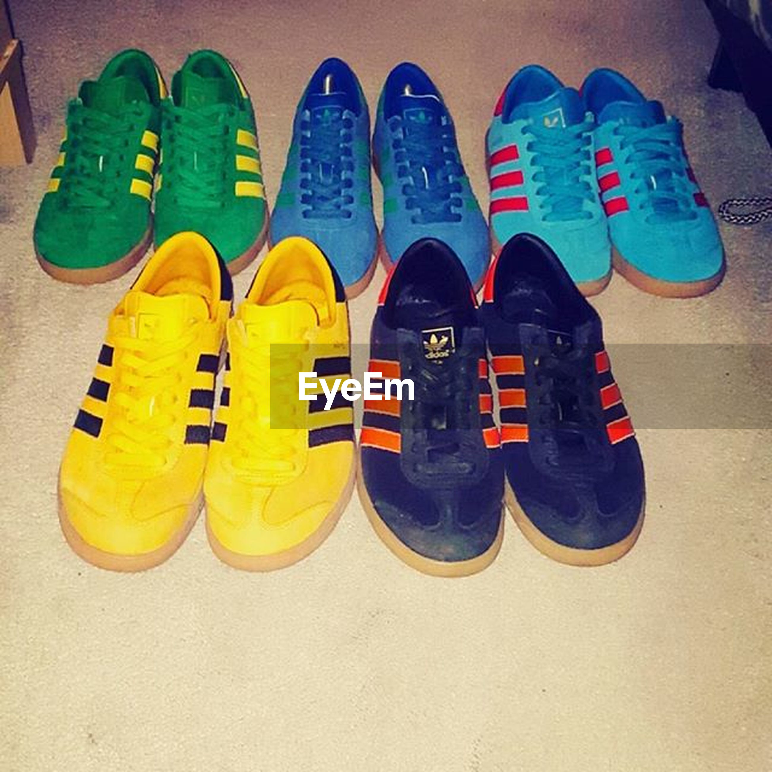 shoe, yellow, still life, high angle view, close-up, indoors, pair, footwear, two objects, side by side, metal, single object, no people, blue, multi colored, sport, black color, variation, in a row, man made object