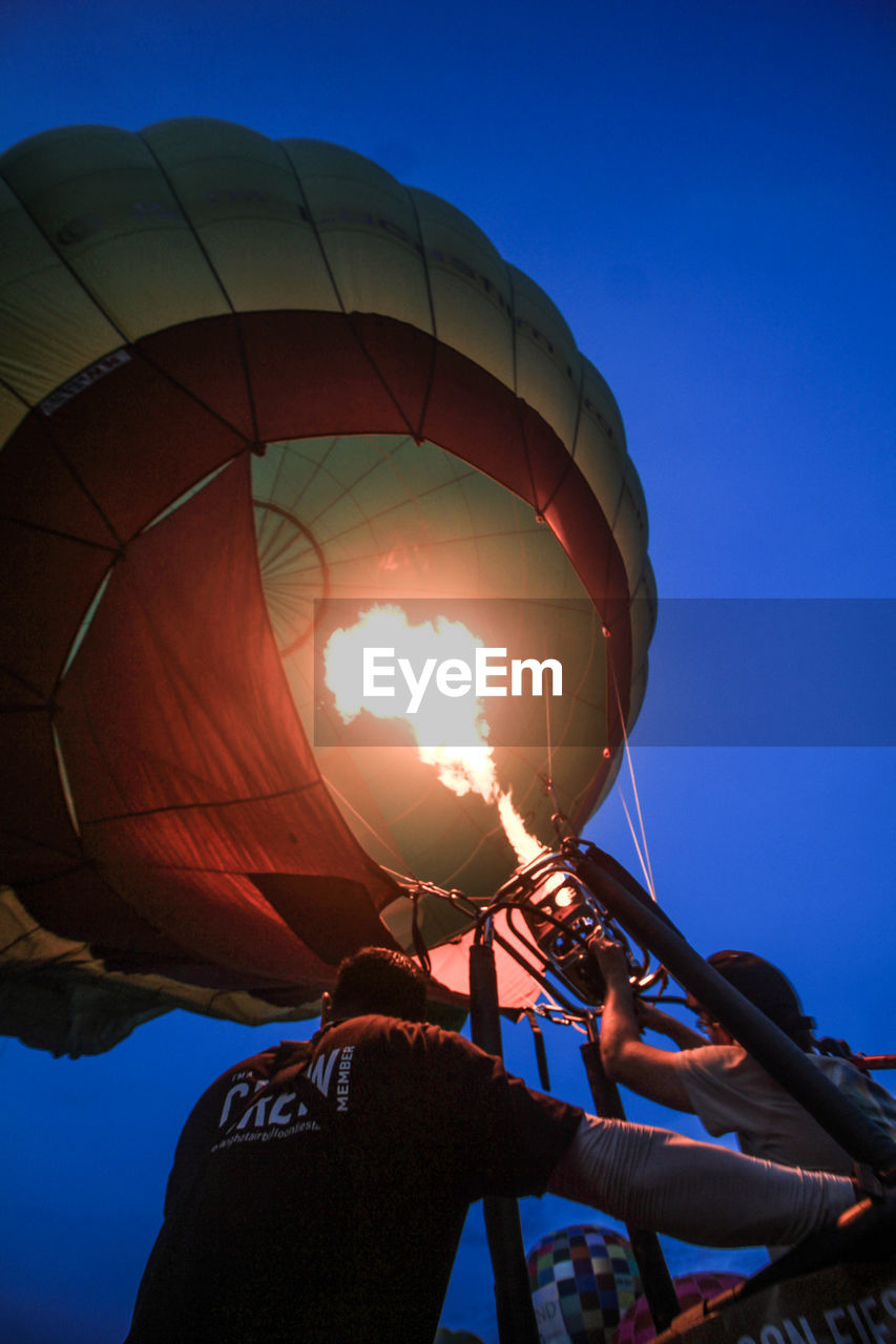 real people, sky, balloon, low angle view, men, lifestyles, hot air balloon, people, leisure activity, nature, clear sky, day, blue, sunlight, adventure, rear view, holding, air vehicle, extreme sports, outdoors