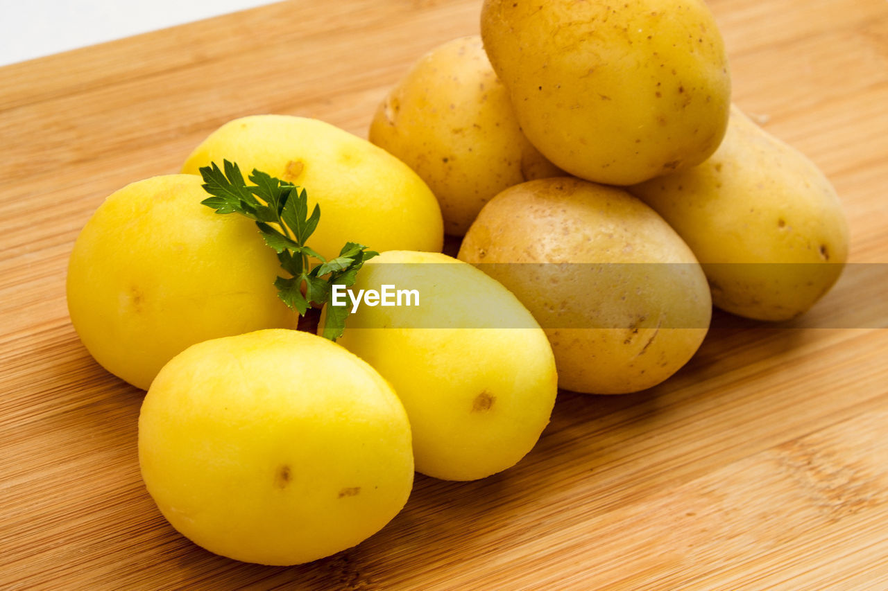 food, food and drink, healthy eating, freshness, table, wellbeing, yellow, fruit, wood - material, still life, close-up, indoors, potato, no people, high angle view, cutting board, group of objects, vegetable, ready-to-eat, plate, vegetarian food