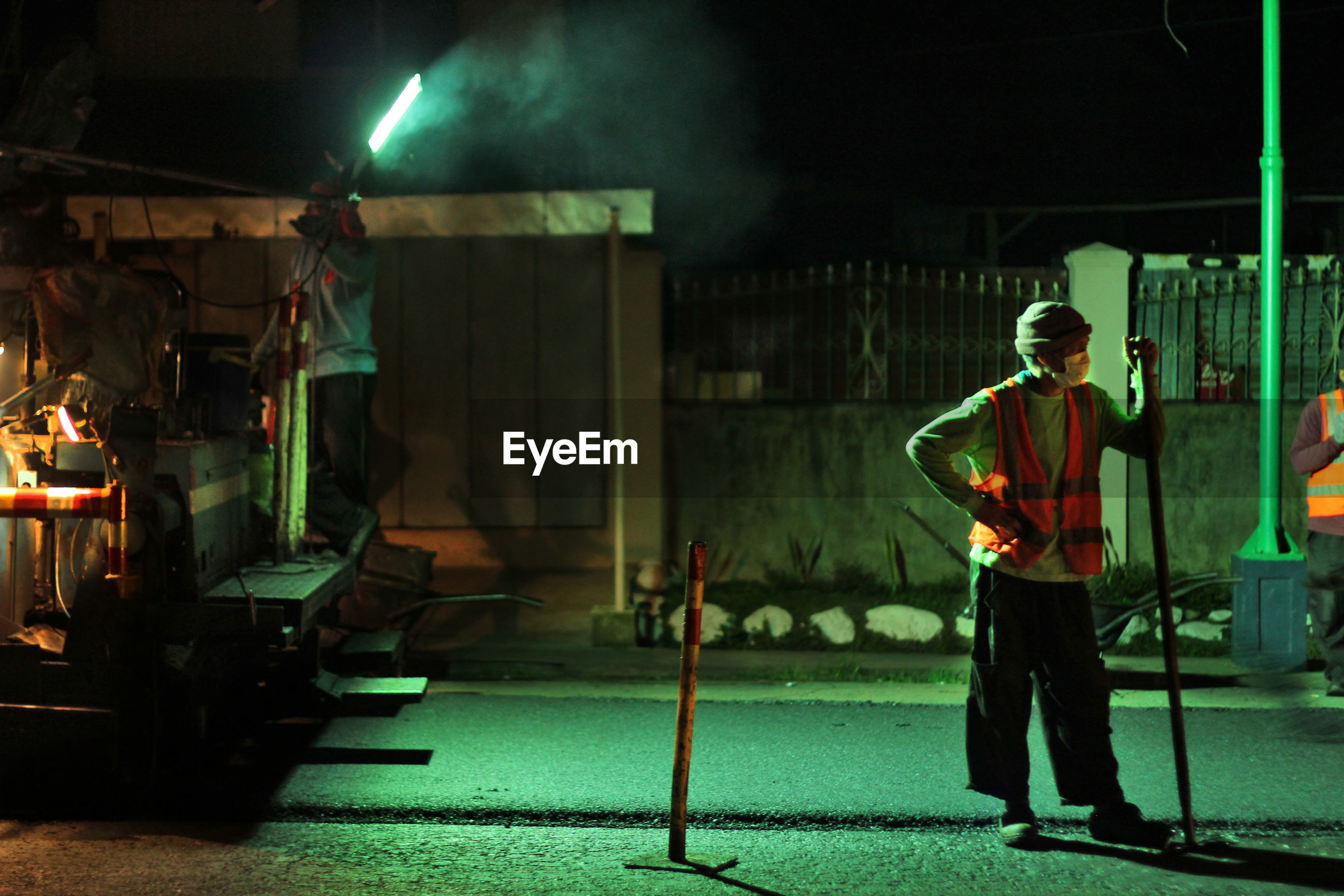 FULL LENGTH OF MAN WORKING AT ILLUMINATED INDUSTRY