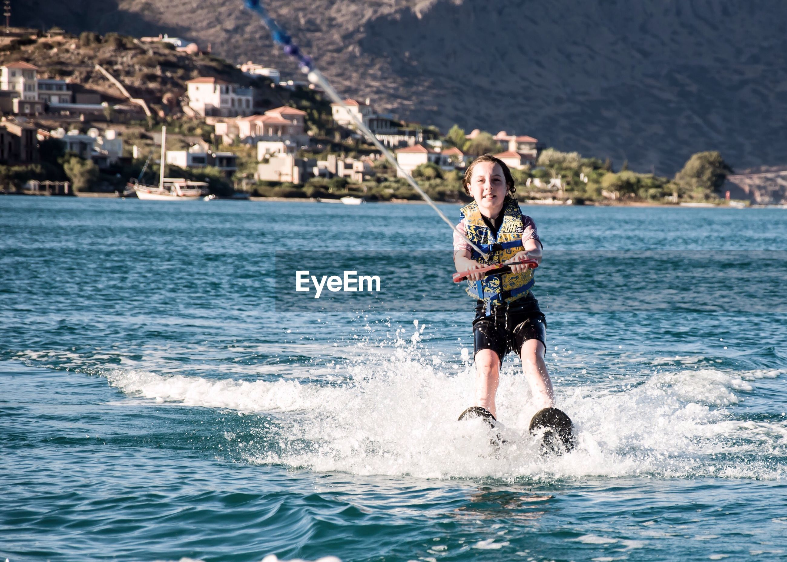 Full length of boy wakeboarding in sea