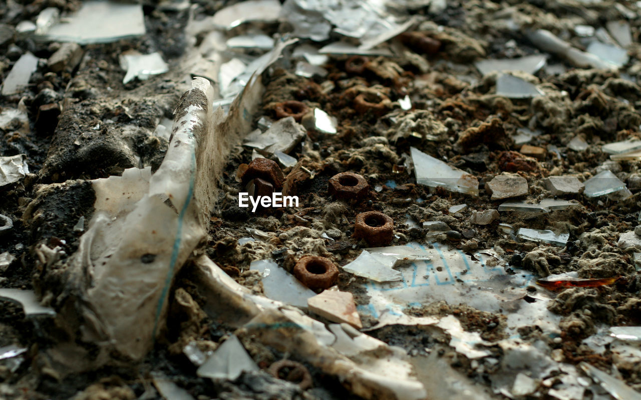 High Angle View Of Rusty Metallic Nuts And Shattered Glass On Dirt