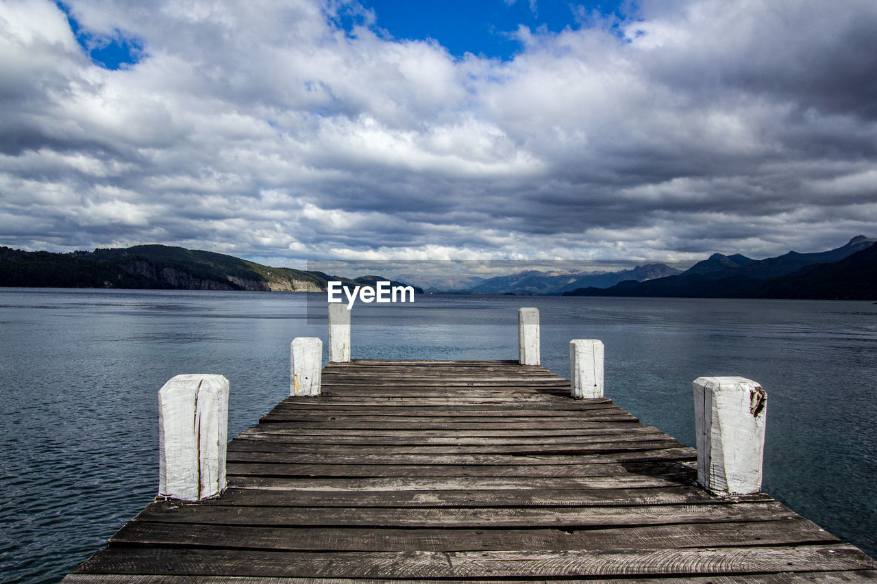 water, sky, cloud - sky, beauty in nature, tranquil scene, tranquility, scenics - nature, wood - material, mountain, sea, pier, direction, idyllic, the way forward, jetty, day, nature, no people, post, outdoors, wooden post, wood paneling, long