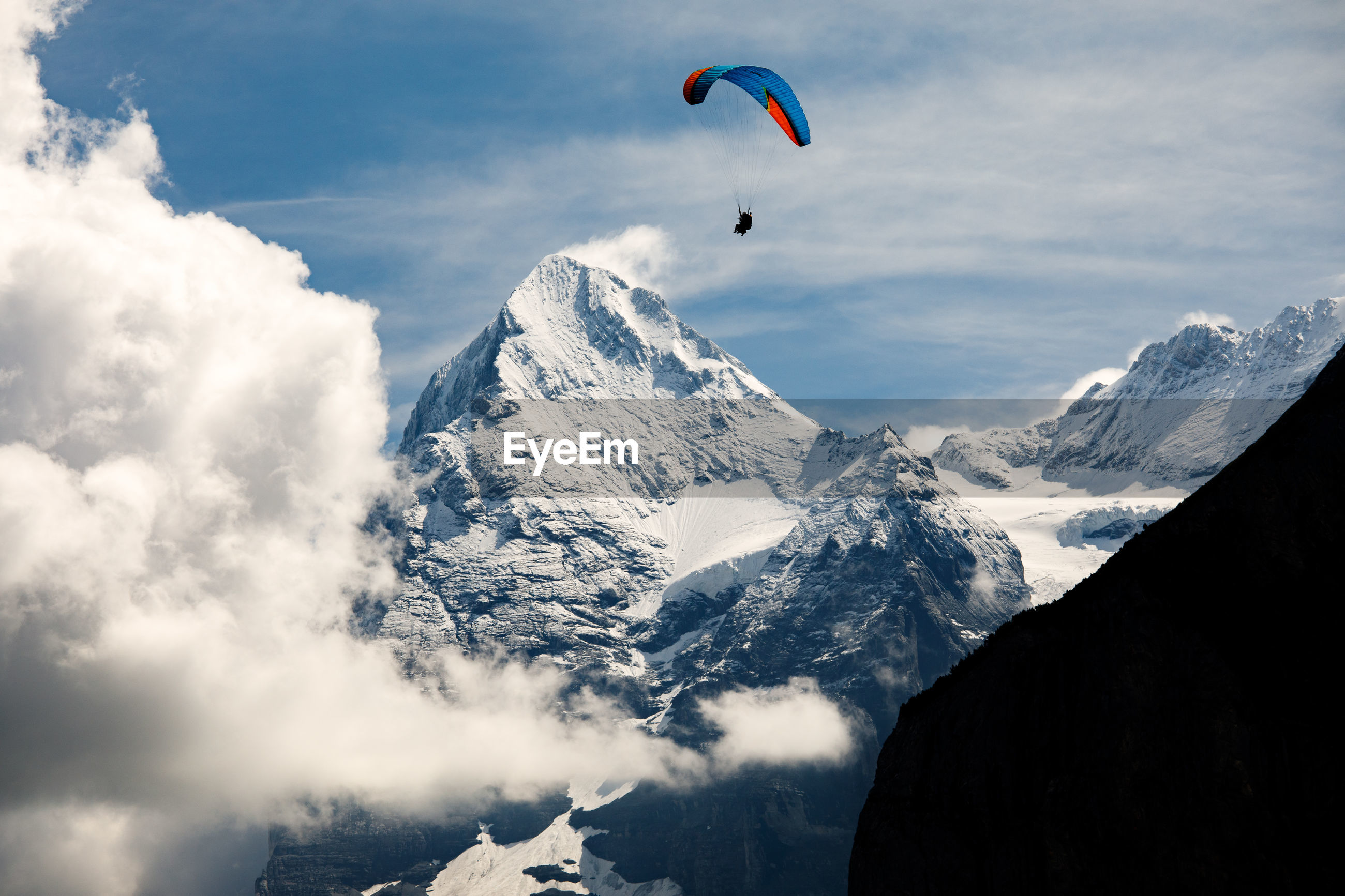 LOW ANGLE VIEW OF PERSON PARAGLIDING AGAINST SNOWCAPPED MOUNTAINS