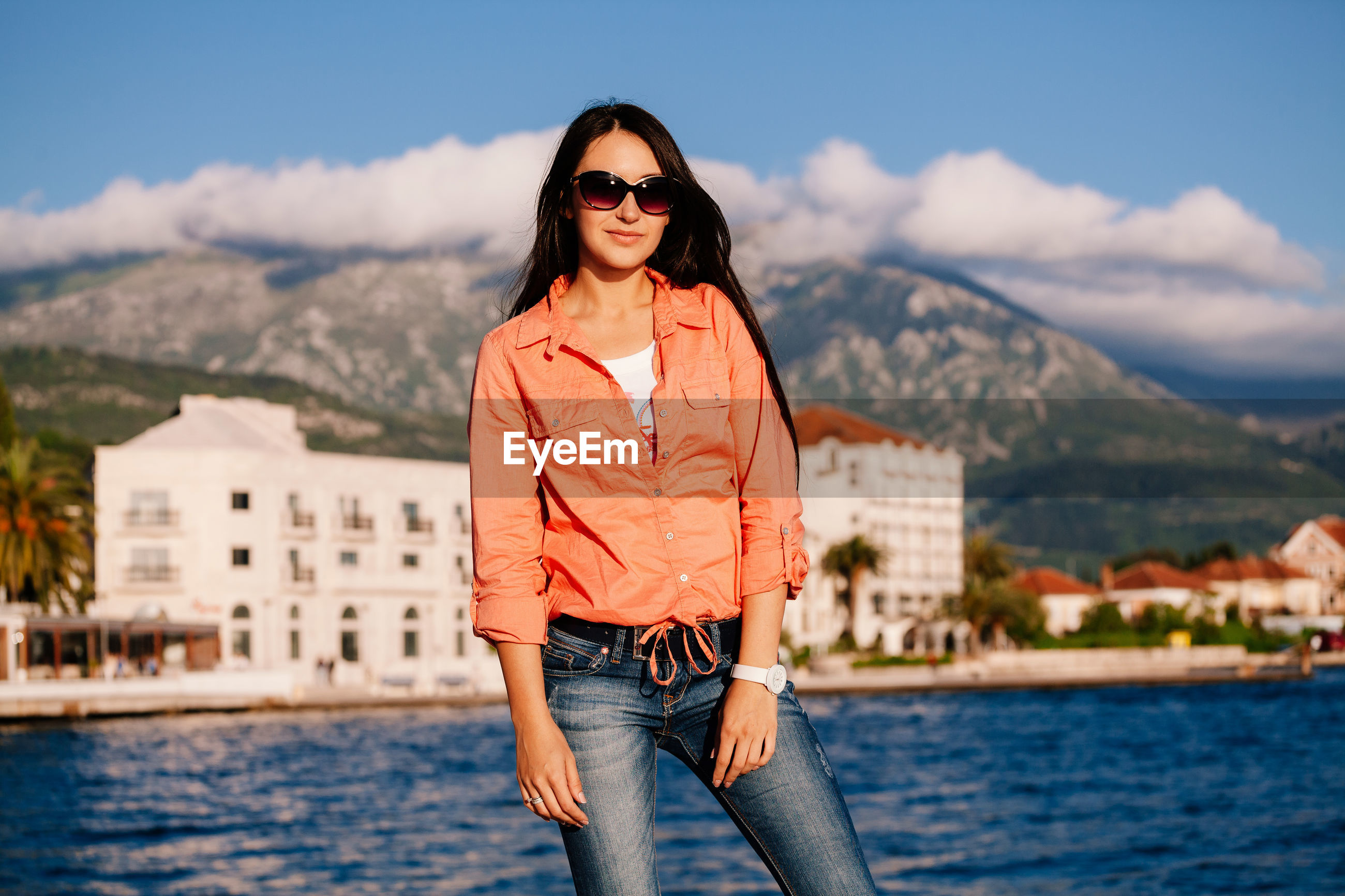 Woman in sunglasses standing at lake against mountains
