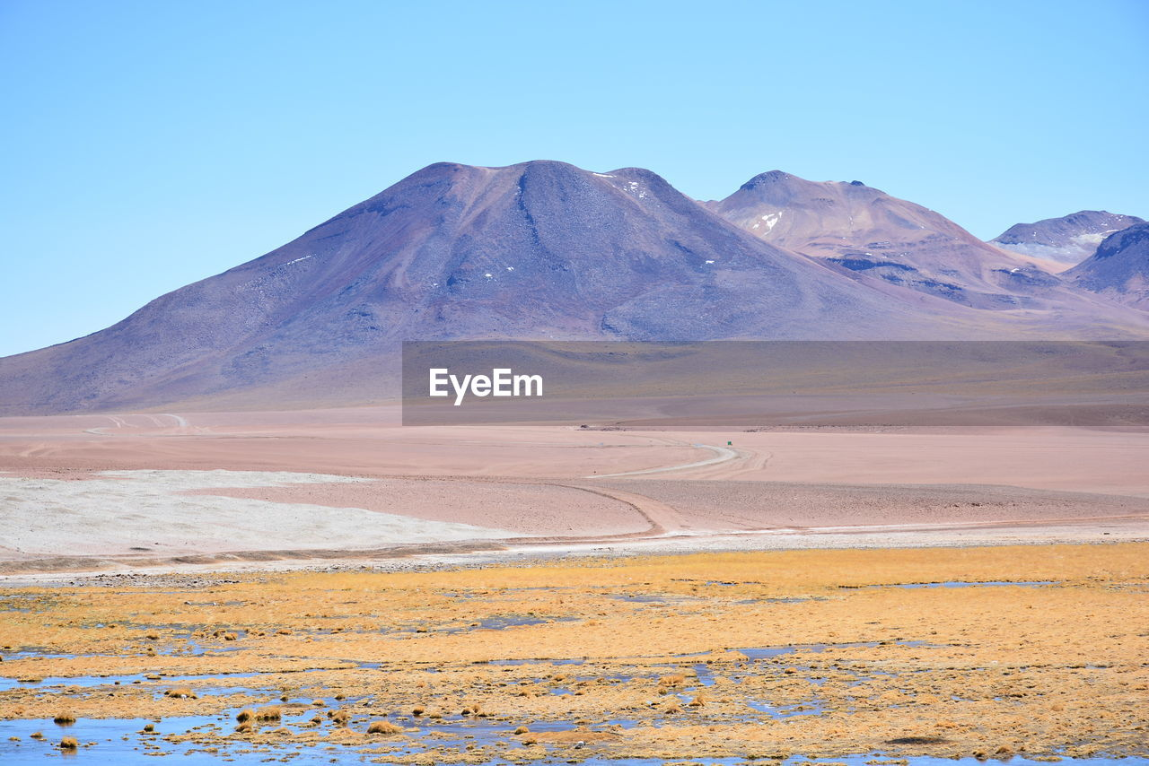 scenics - nature, sky, environment, landscape, mountain, tranquility, tranquil scene, beauty in nature, desert, non-urban scene, land, clear sky, nature, day, no people, idyllic, arid climate, remote, blue, physical geography, mountain range, climate, outdoors, mountain peak, salt flat