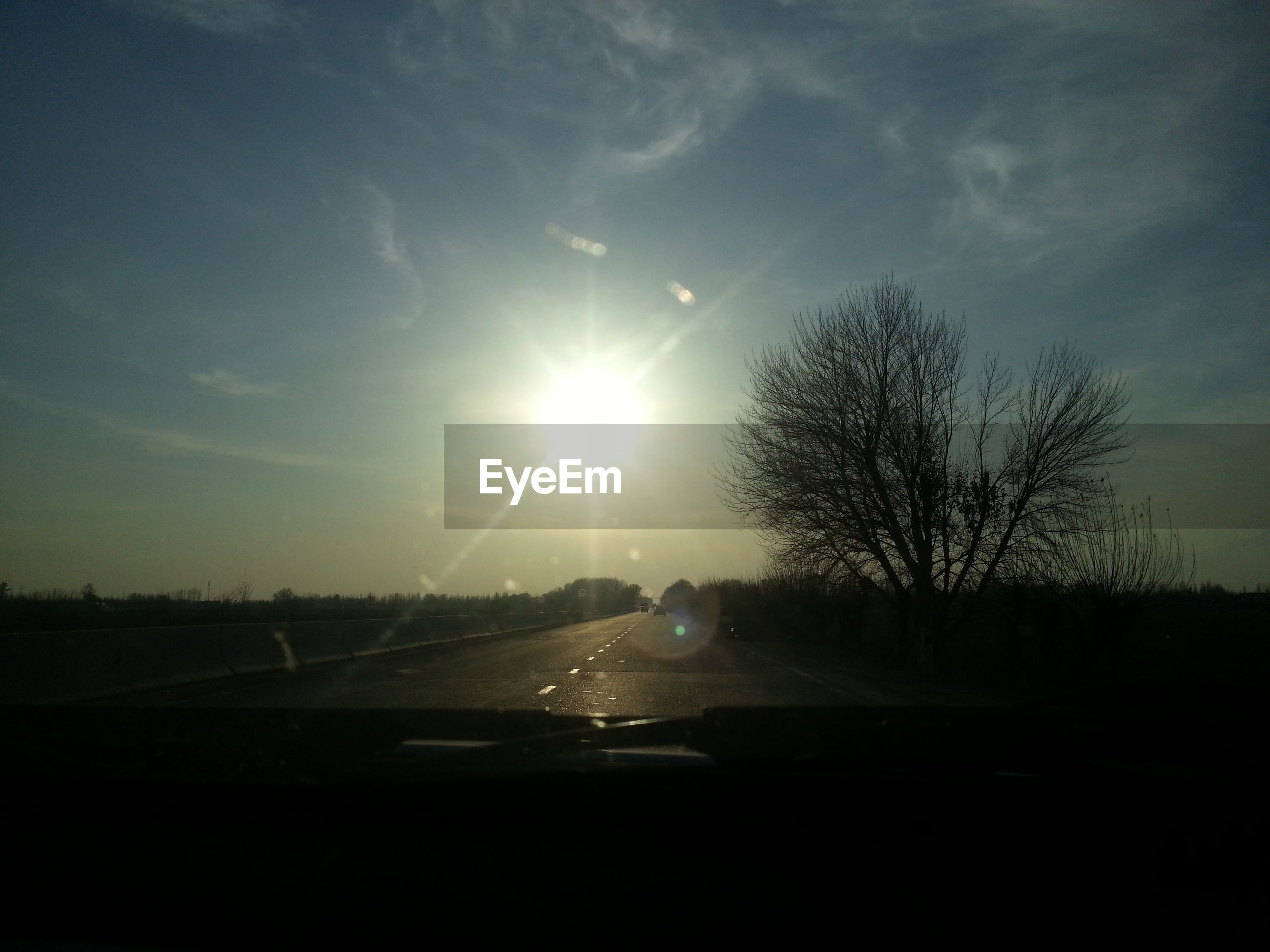 sun, transportation, sunset, silhouette, sky, car, land vehicle, road, lens flare, sunbeam, sunlight, mode of transport, tree, nature, tranquility, landscape, cloud - sky, tranquil scene, beauty in nature, scenics