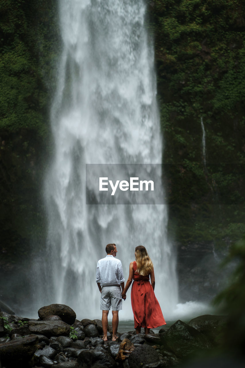 Rear view of people looking at waterfall in forest