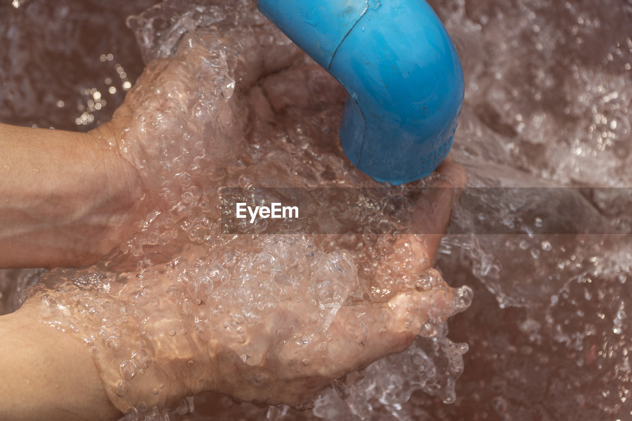 HIGH ANGLE VIEW OF PERSON HAND HOLDING WET GLASS