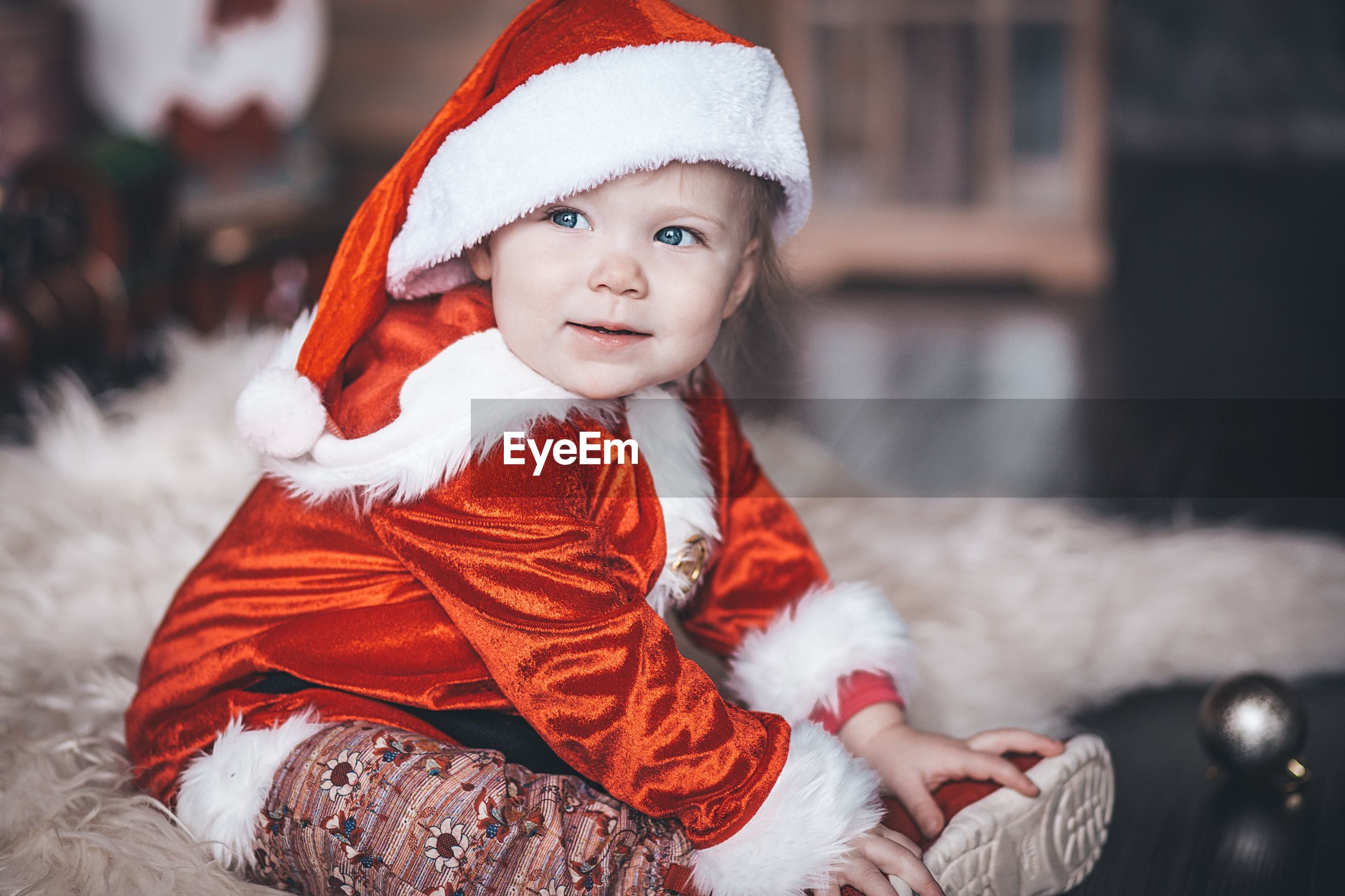 Baby in santa claus clothes sits by the christmas tree