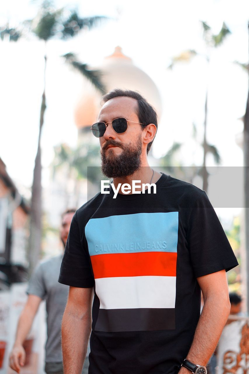 beard, facial hair, standing, one person, sunglasses, real people, young men, focus on foreground, glasses, lifestyles, waist up, front view, young adult, fashion, casual clothing, day, leisure activity, portrait, men, outdoors