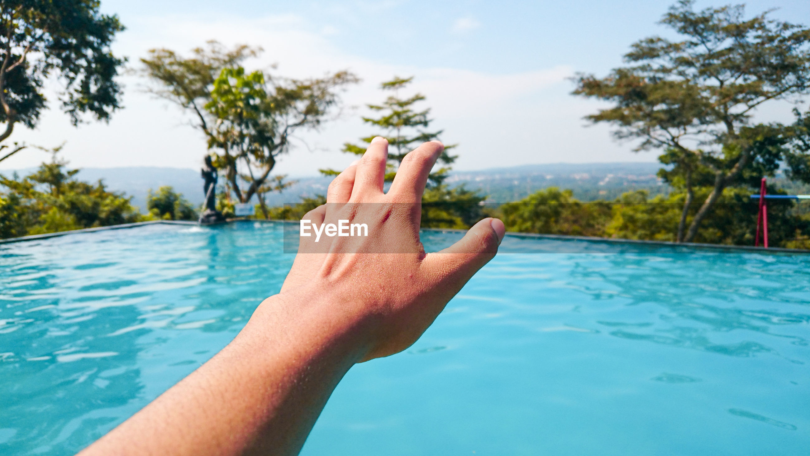 Cropped image of hand against swimming pool