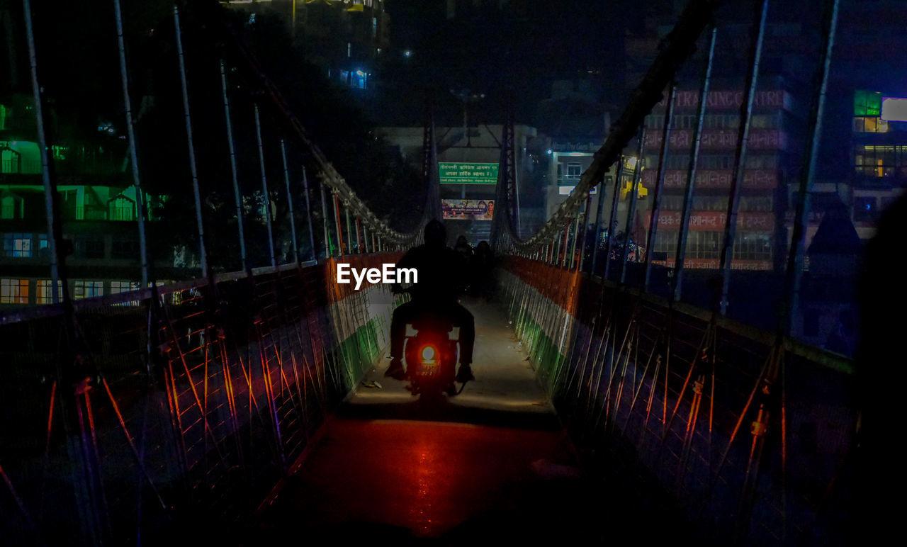 REAR VIEW OF MAN STANDING ON ILLUMINATED BRIDGE