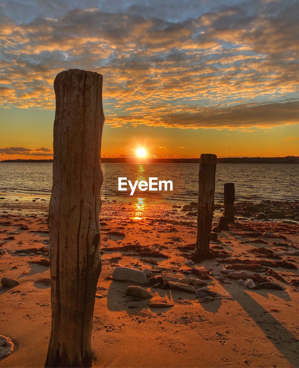 sunset, sky, water, beach, sea, beauty in nature, land, scenics - nature, cloud - sky, tranquility, tranquil scene, orange color, wood - material, nature, post, no people, horizon, idyllic, horizon over water, sun, wooden post, outdoors