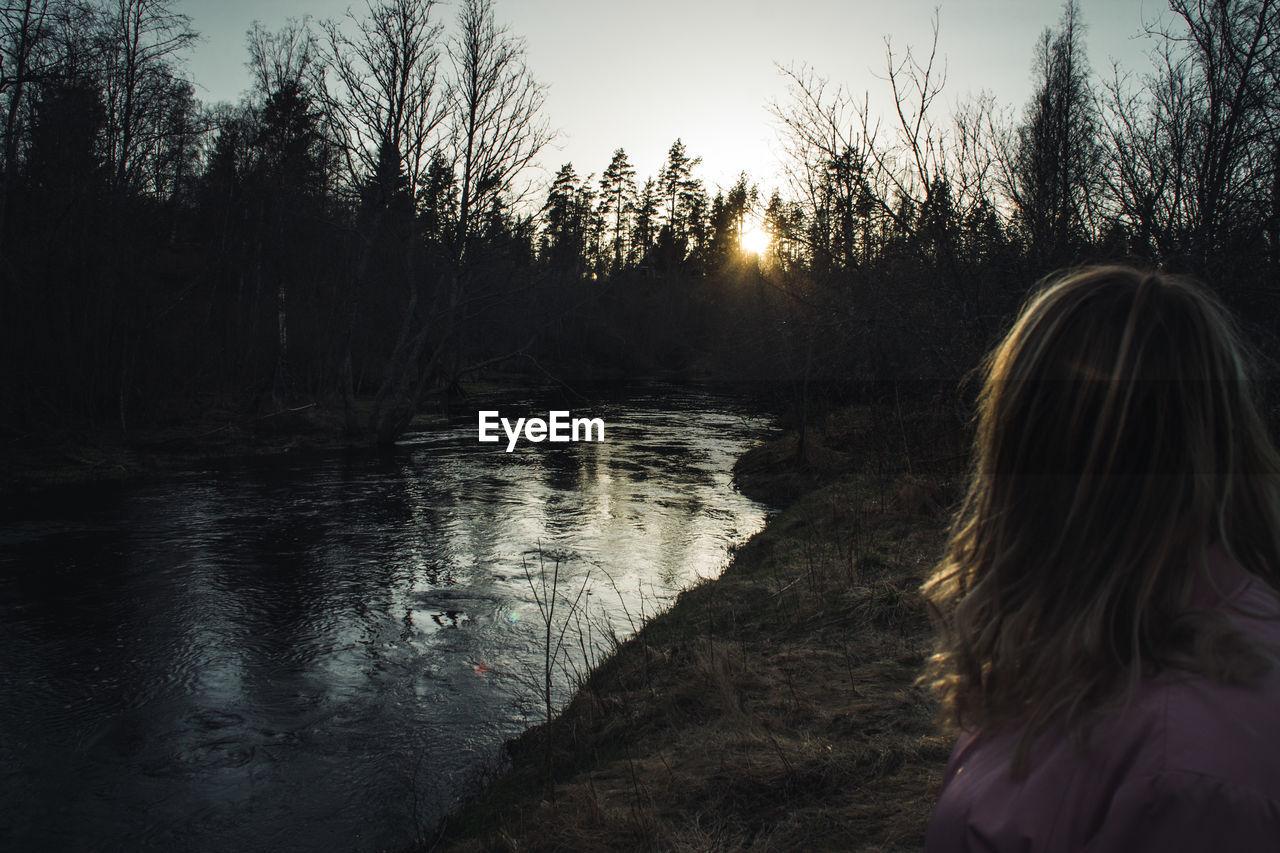 Woman at lakeshore during sunset