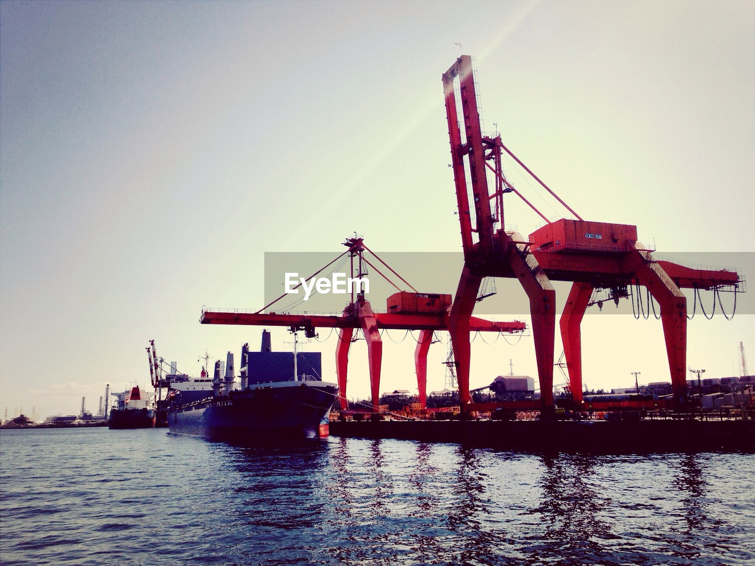 water, waterfront, sunset, sea, clear sky, silhouette, transportation, nautical vessel, crane - construction machinery, sky, built structure, commercial dock, harbor, reflection, crane, boat, copy space, nature, mode of transport, dusk