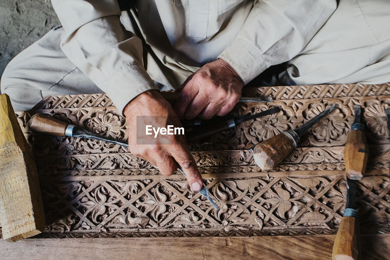 Midsection Of Man Carving Wood