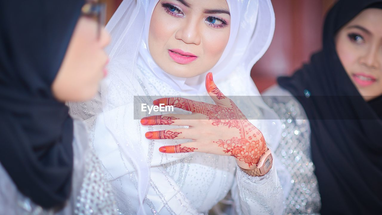 young women, traditional clothing, real people, young adult, celebration, wedding, beautiful woman, togetherness, bride, leisure activity, two people, wedding dress, celebration event, smiling, standing, lifestyles, life events, indoors, veil, close-up, women, happiness, beauty, portrait, day, friendship, adult, people