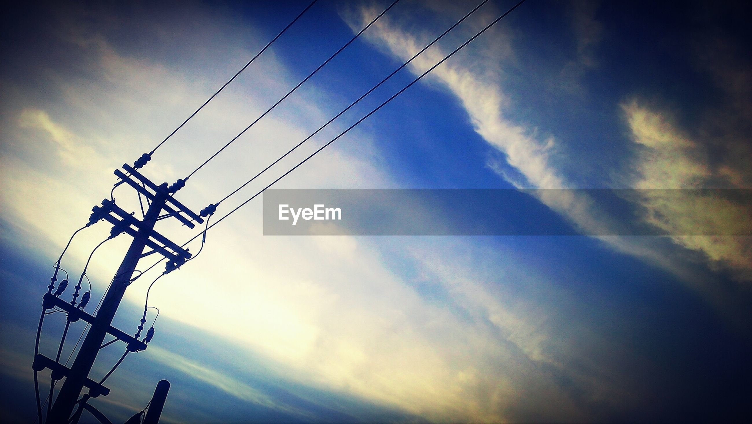 High section of electricity pylon against clouds