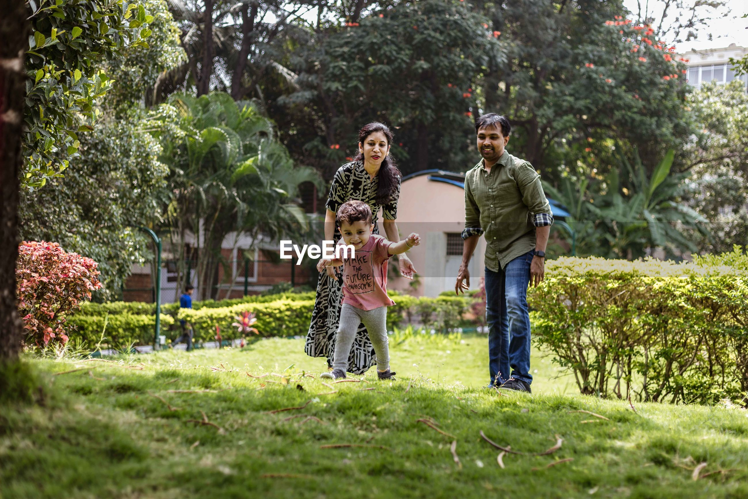 Parents looking at cute son running on grassy land in park