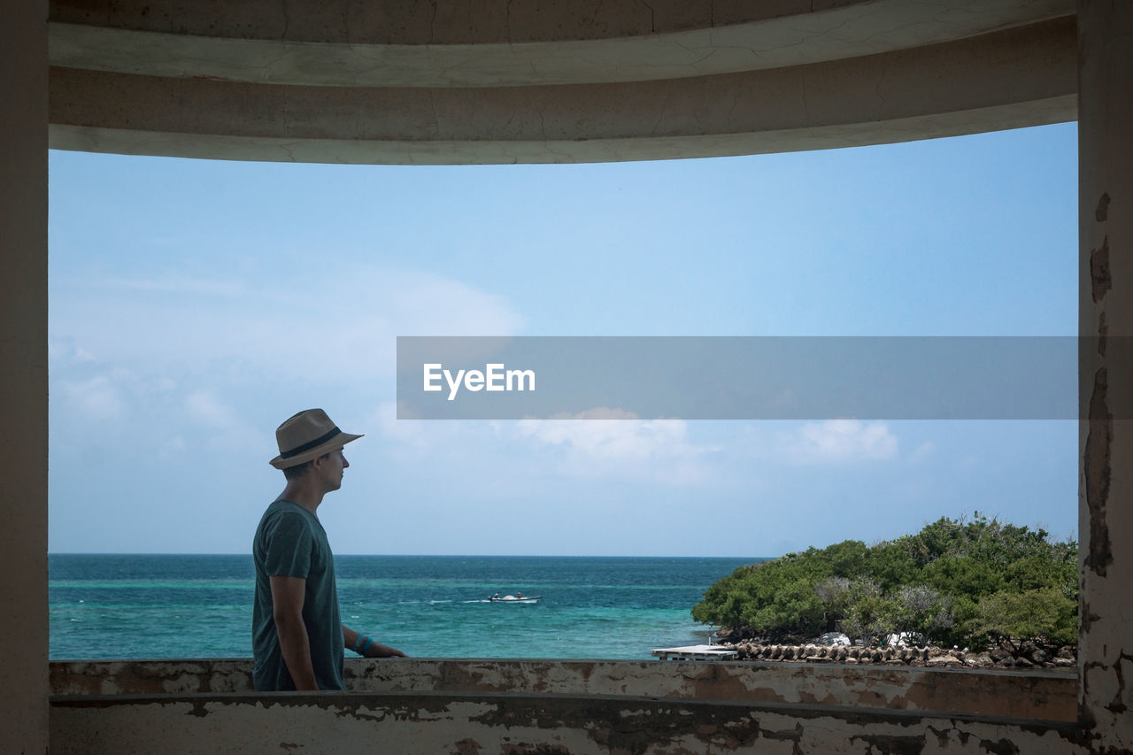 sky, hat, sea, water, horizon, horizon over water, nature, beauty in nature, scenics - nature, real people, beach, land, day, one person, clothing, cloud - sky, lifestyles, tranquility, outdoors, sun hat, looking at view