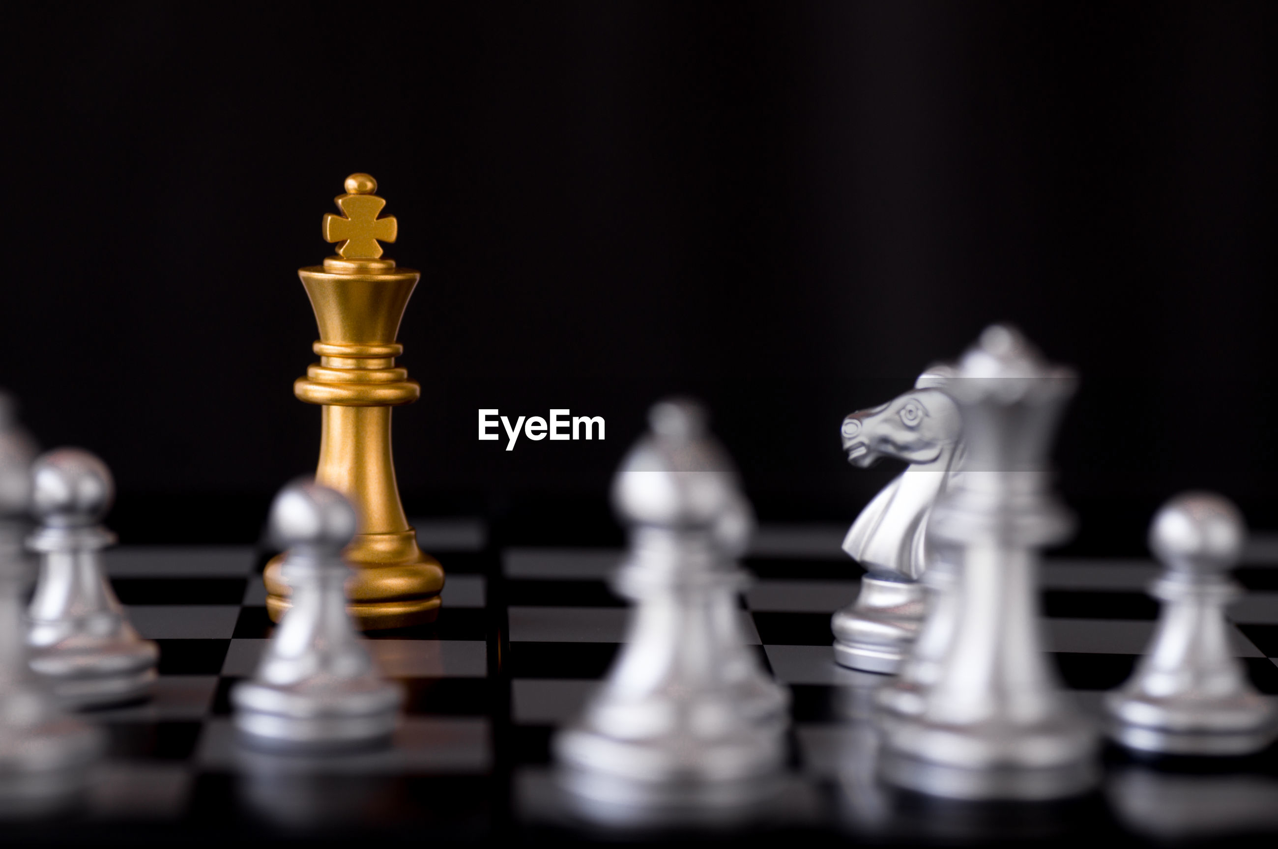 Close-up of game pieces on chess board against black background