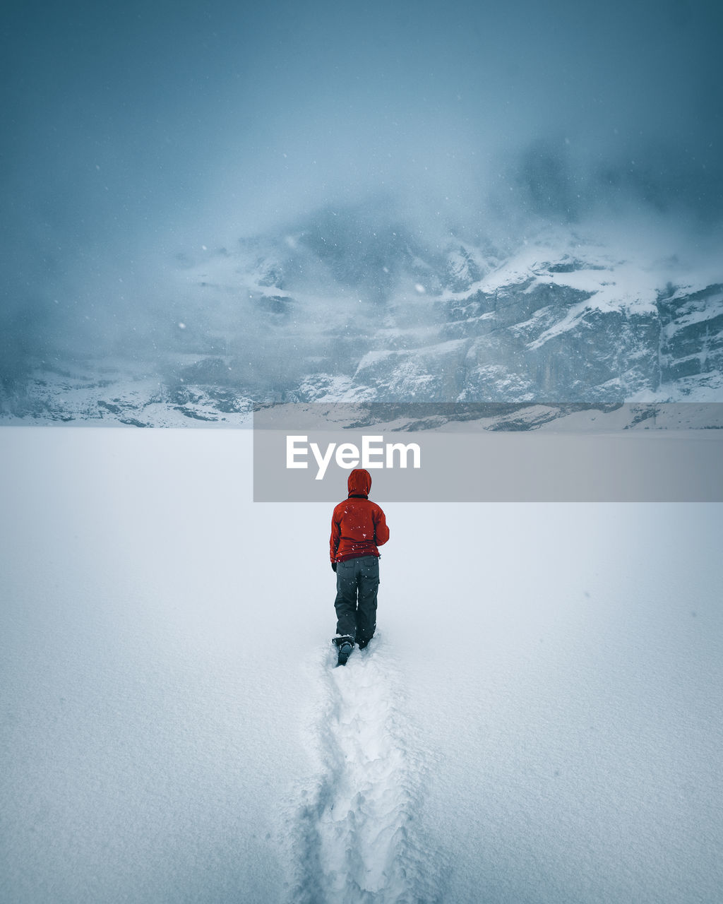 Woman walking on snow covered mountain against sky