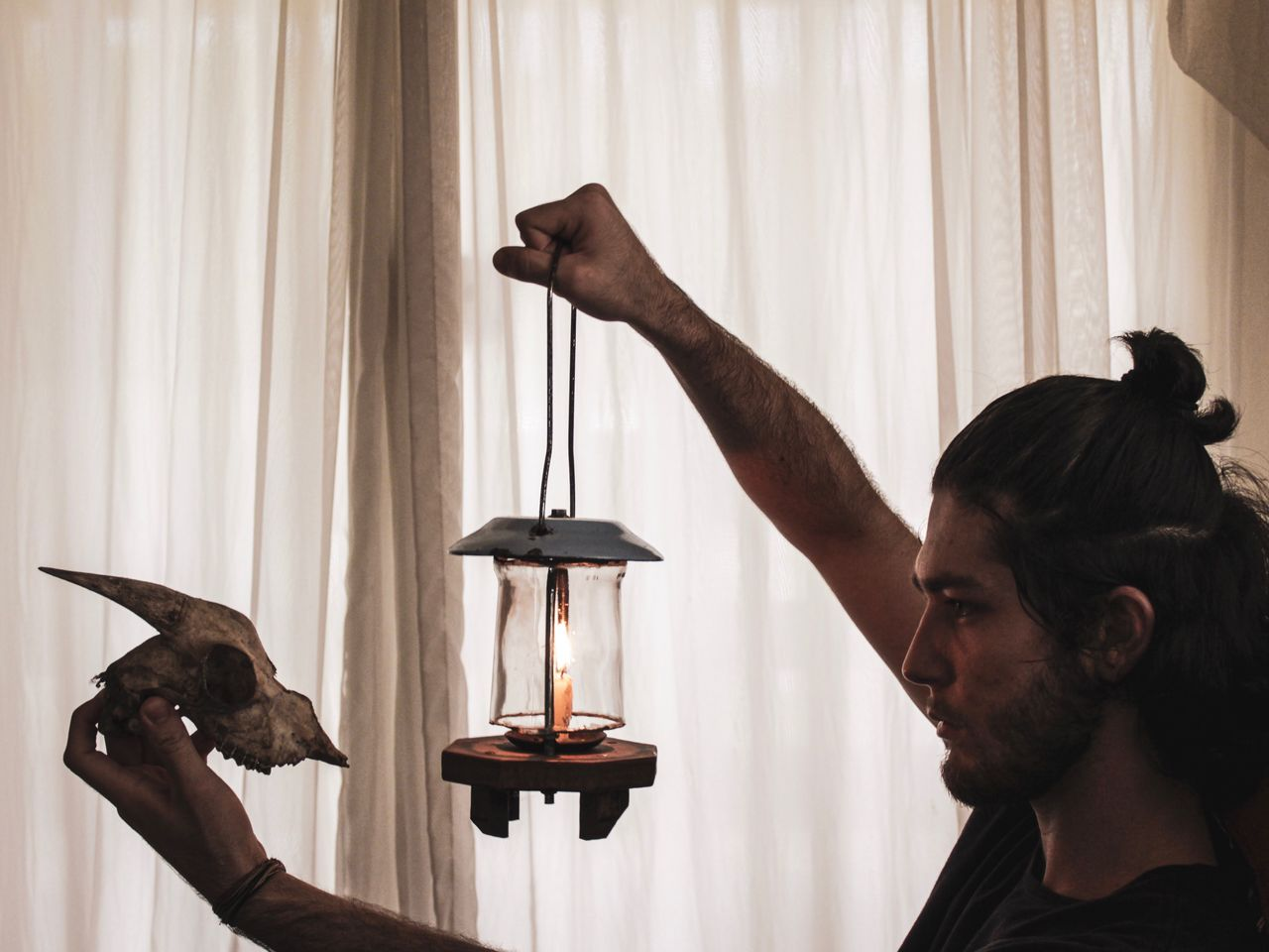 Profile view of young man holding animal skull and lantern against white curtain