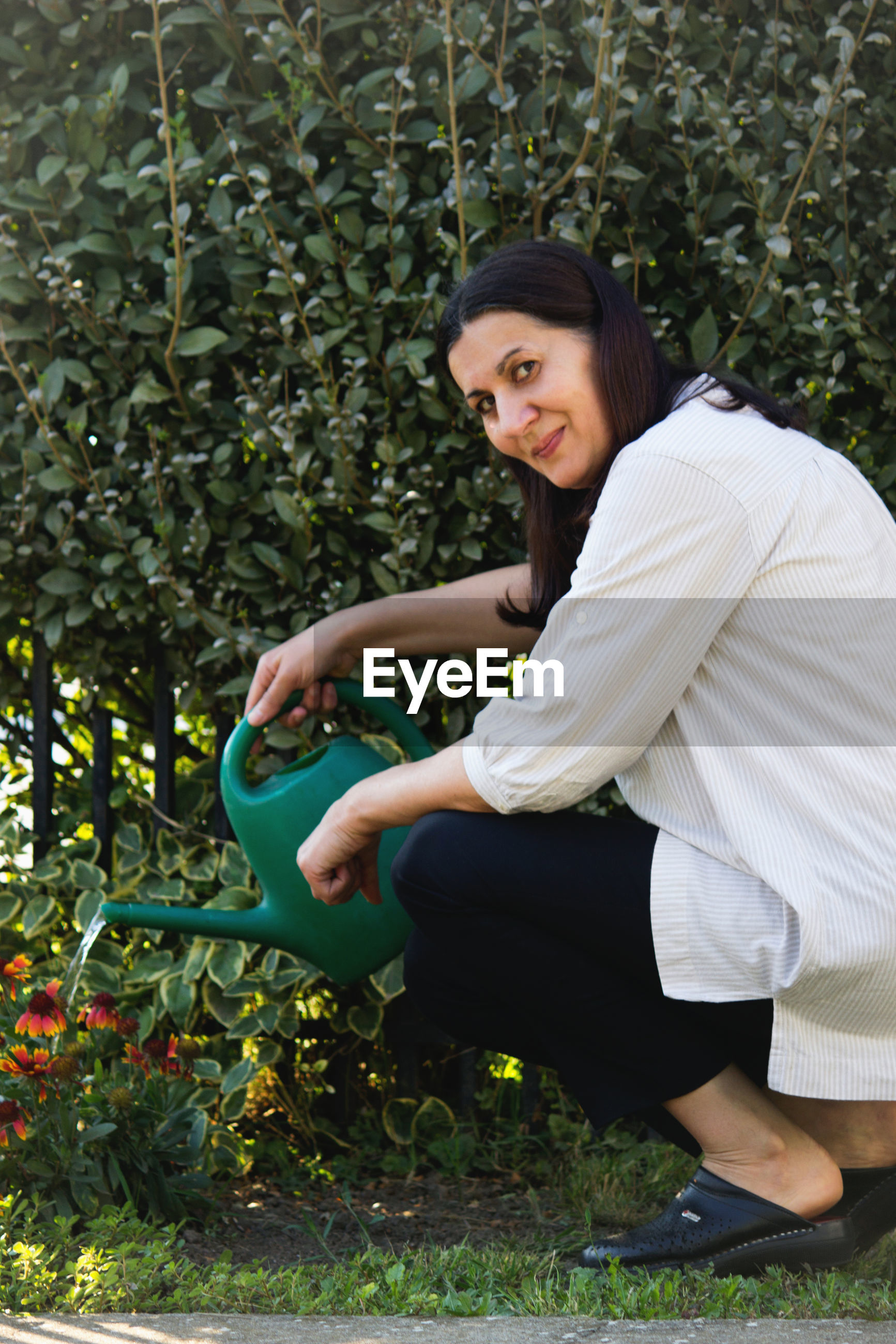 Portrait of woman crouching while watering plants