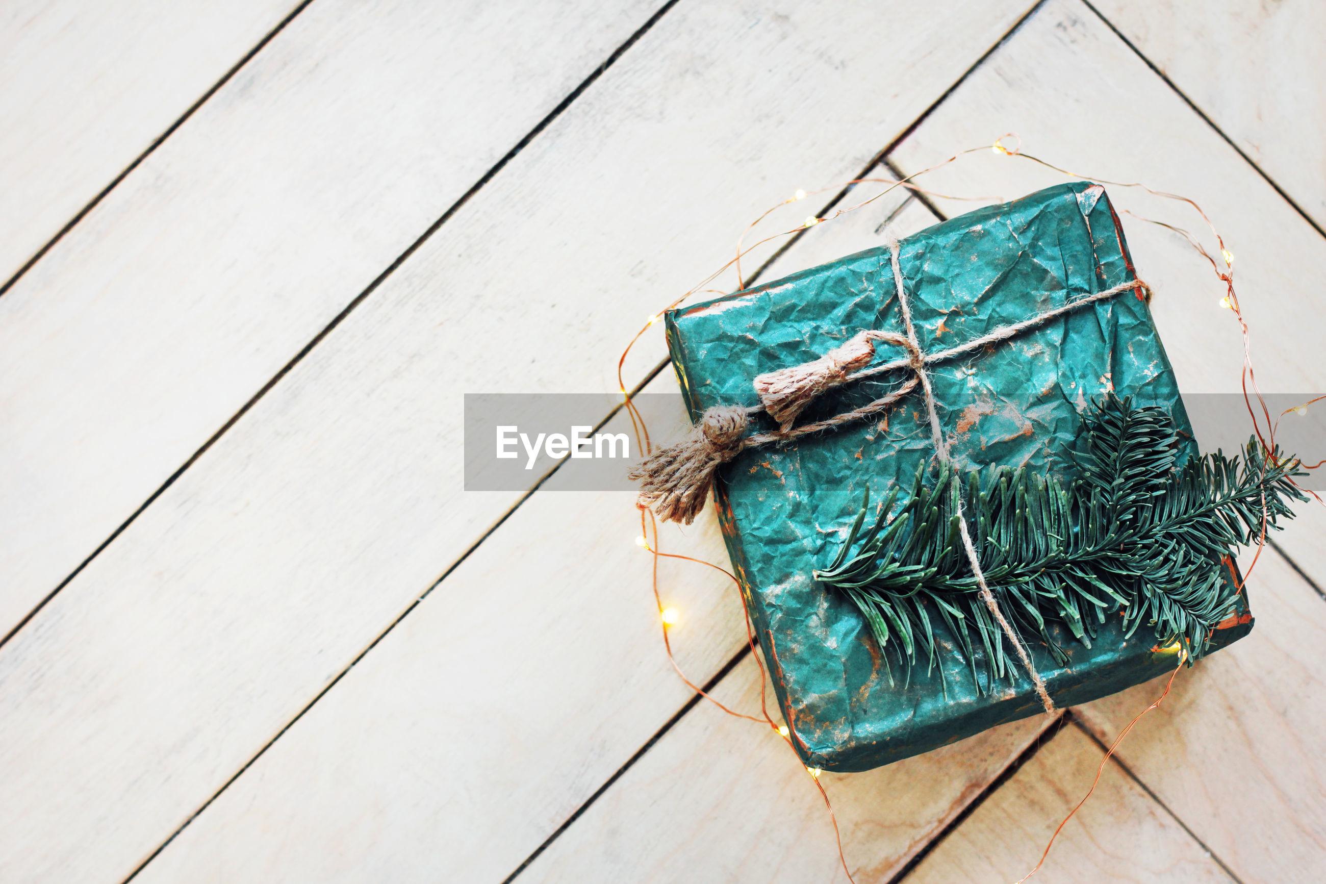 High angle view of christmas gift and string light on hardwood floor