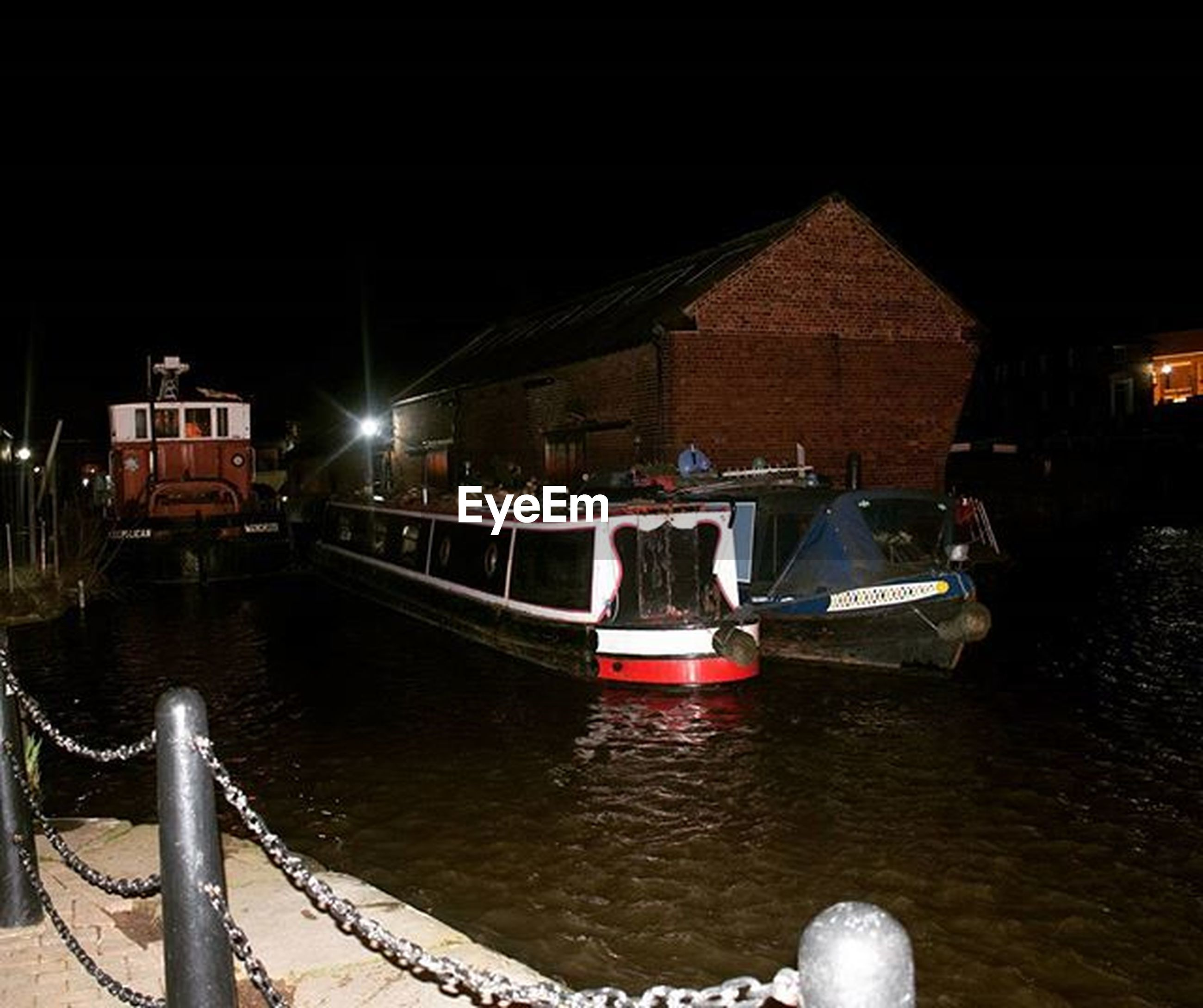 nautical vessel, water, transportation, mode of transport, boat, night, moored, built structure, illuminated, building exterior, architecture, reflection, canal, river, clear sky, waterfront, travel, outdoors, harbor, city