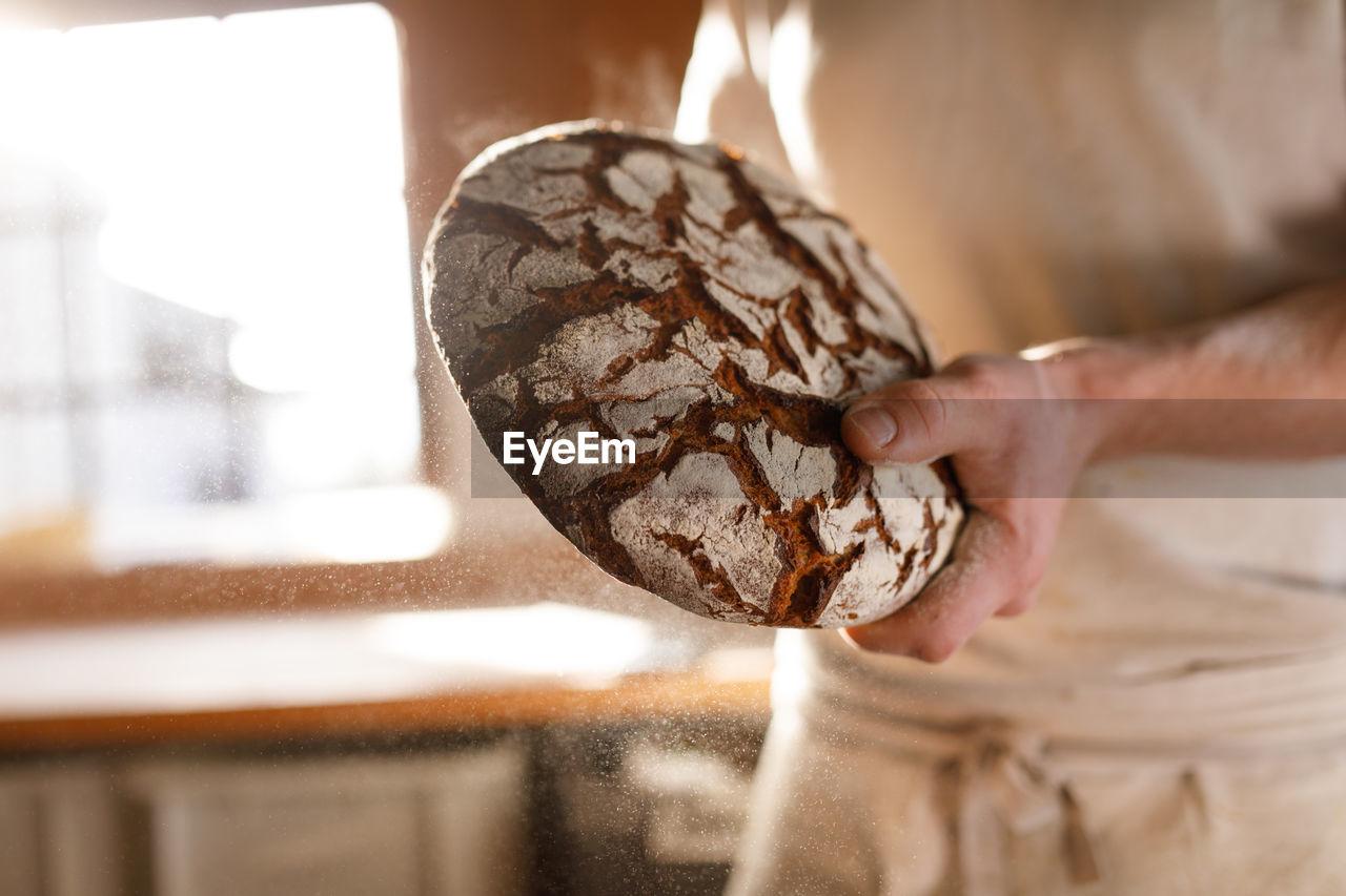 Baker holding round bread in back-lit