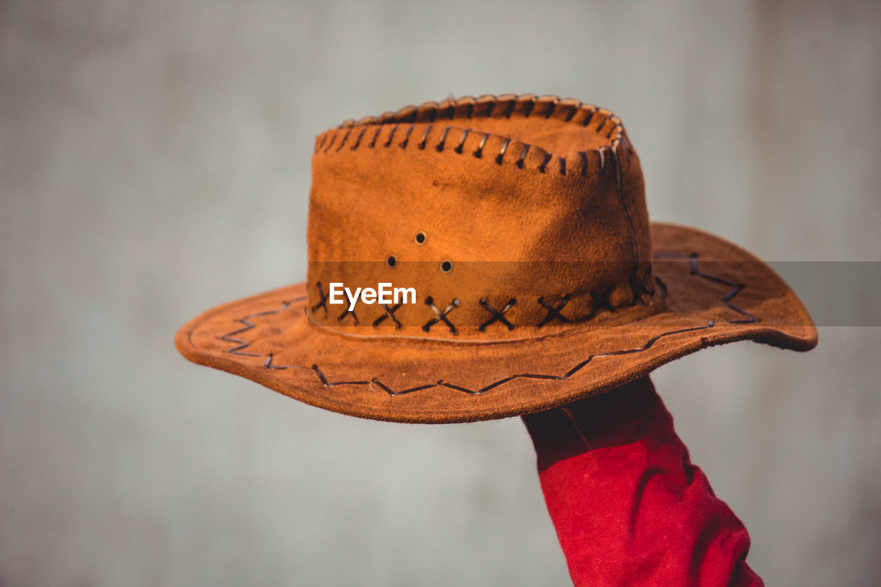 focus on foreground, close-up, hat, one person, unrecognizable person, day, brown, red, clothing, shoe, human body part, orange color, lifestyles, wood - material, old, indoors, body part, leather, human limb