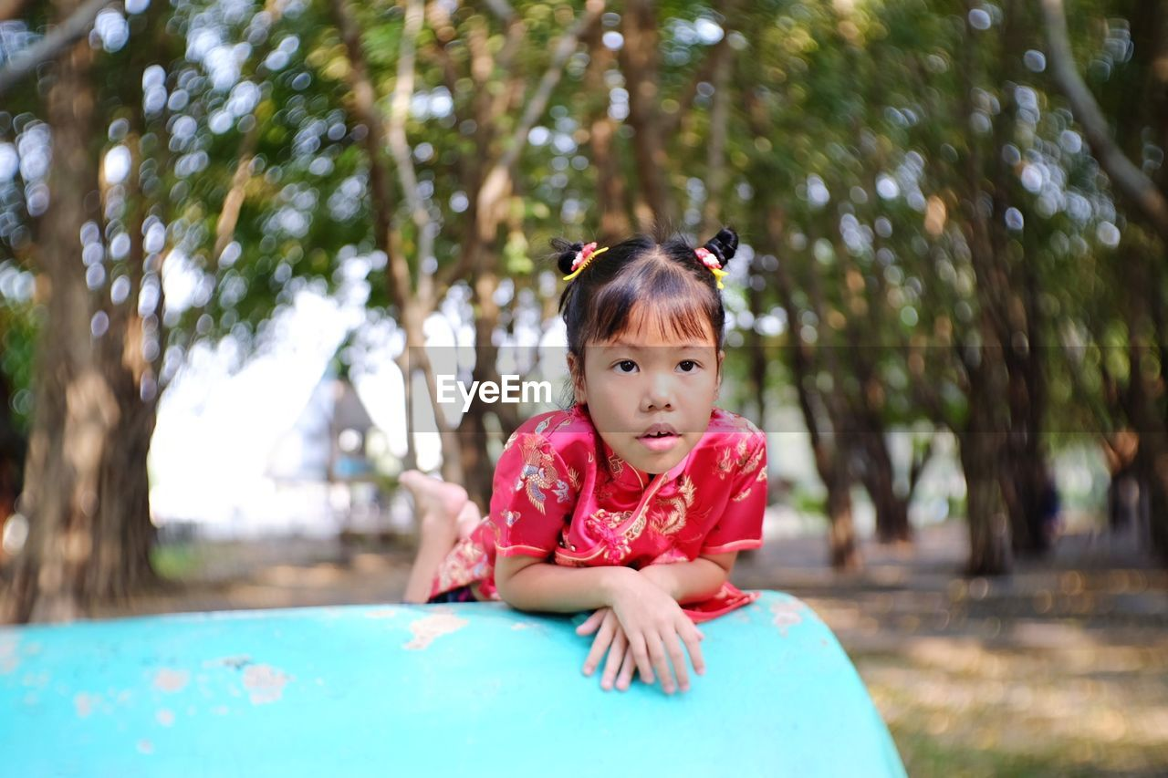 Cute Girl Lying On Playing Equipment At Playground