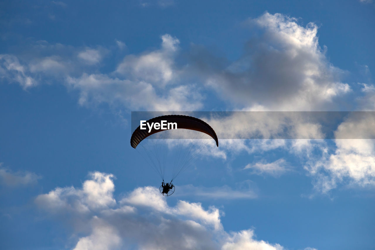 extreme sports, cloud - sky, sky, adventure, mid-air, parachute, sport, low angle view, paragliding, unrecognizable person, flying, one person, leisure activity, real people, day, joy, transportation, gliding, freedom, lifestyles, outdoors