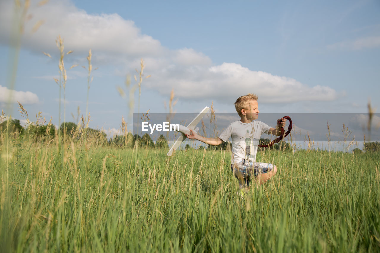 field, grass, sky, nature, one person, growth, standing, day, outdoors, cloud - sky, real people, beauty in nature, childhood, people