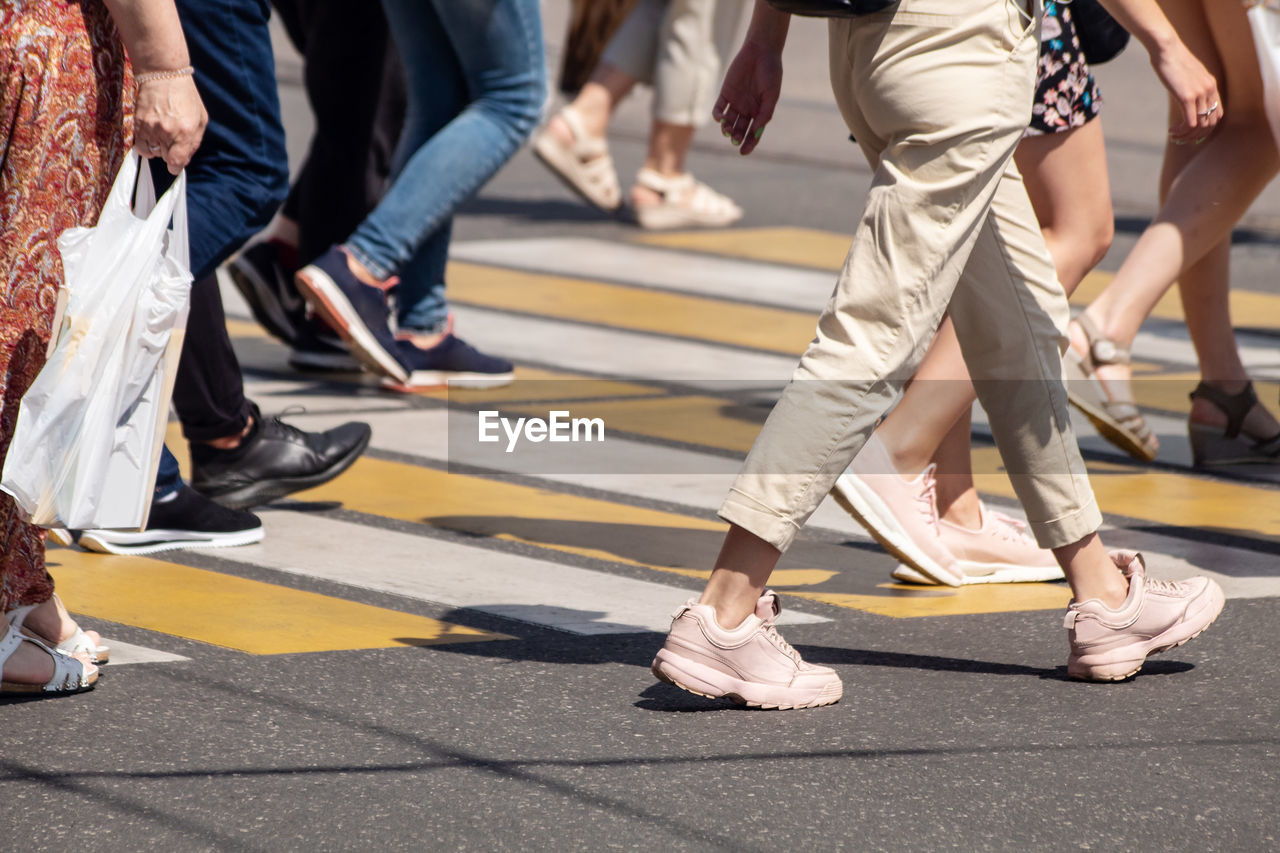 group of people, low section, city, street, human body part, body part, human leg, real people, day, shoe, walking, road, lifestyles, men, transportation, group, medium group of people, people, outdoors, leisure activity, human foot