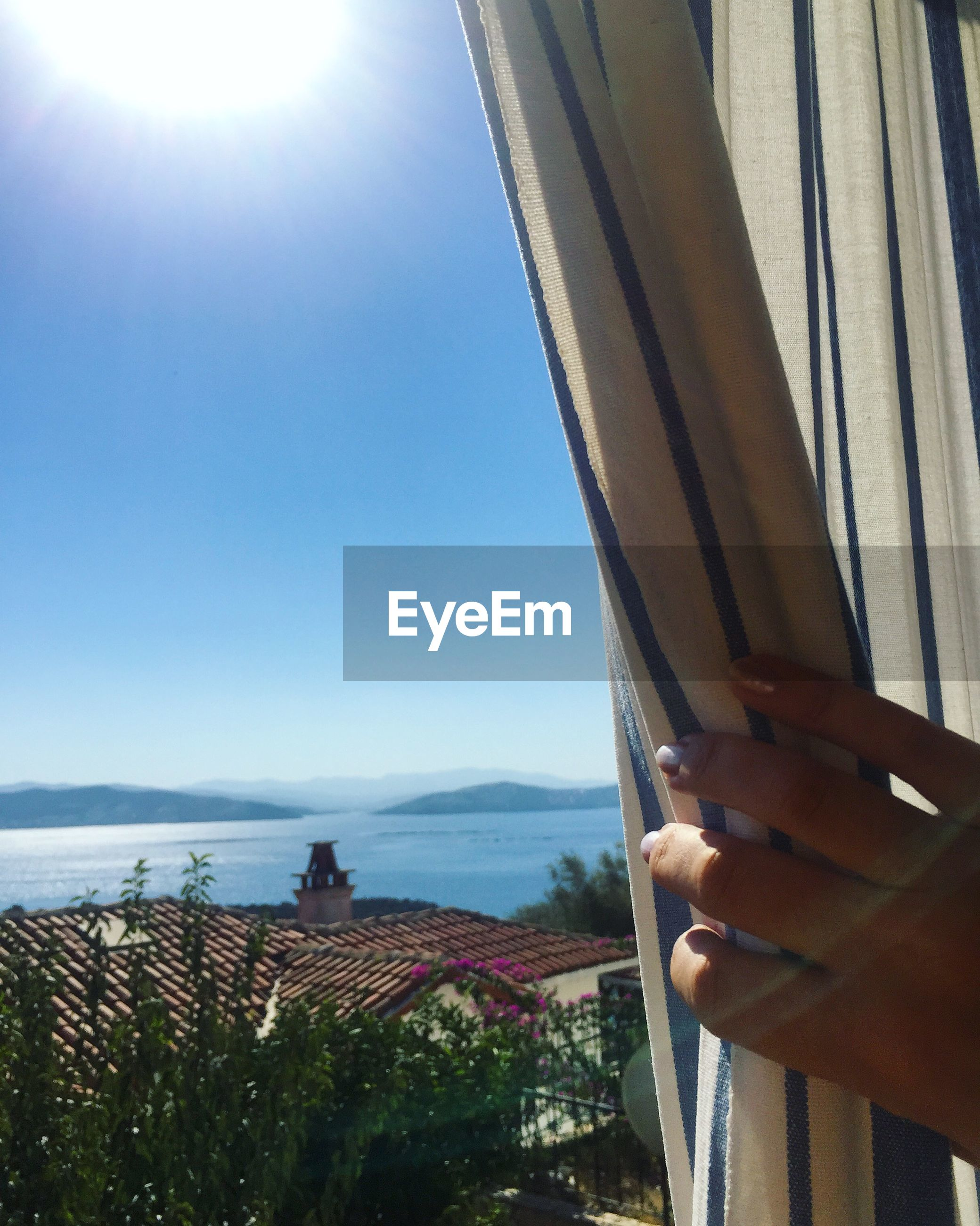 Cropped image of hand on curtain against sky