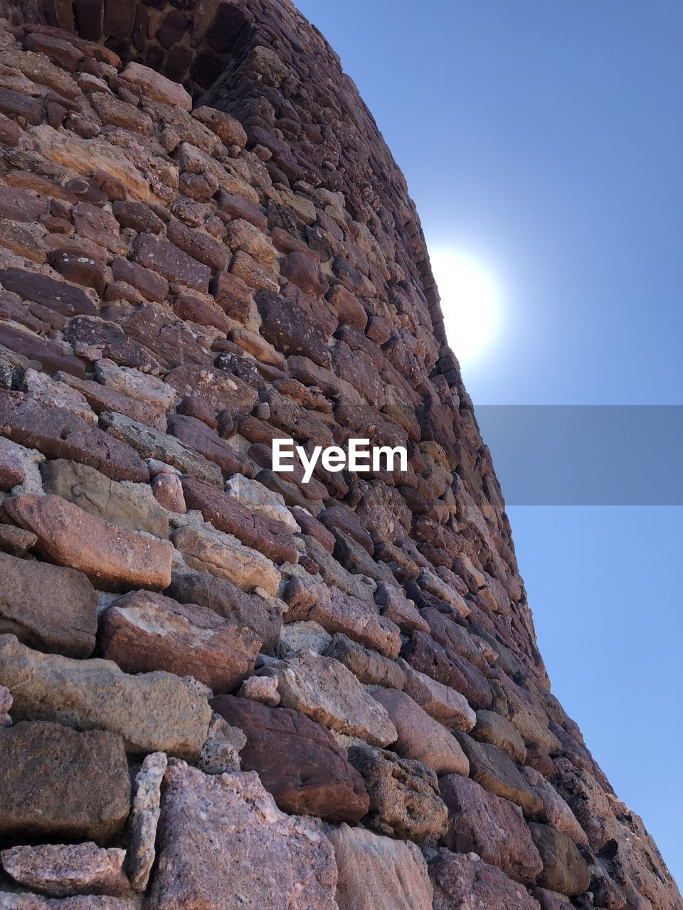 sky, low angle view, rock, solid, day, nature, rock - object, no people, clear sky, textured, rough, sunlight, rock formation, outdoors, beauty in nature, geology, mountain, tranquility, close-up, physical geography, formation, eroded