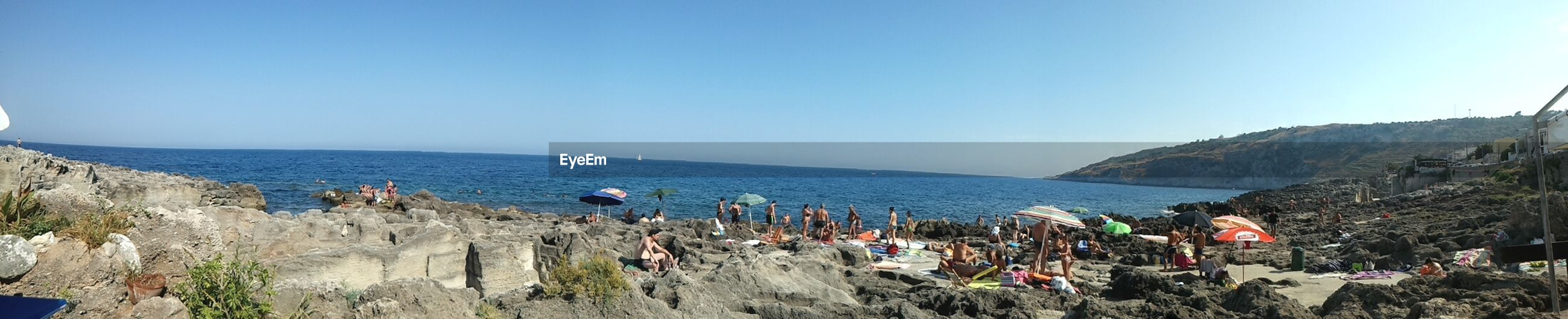 Panoramic view people standing on rocky shore