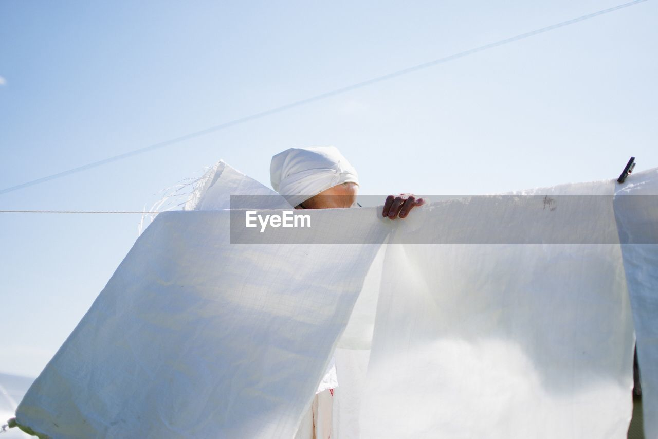 Senior woman behind white clothes drying