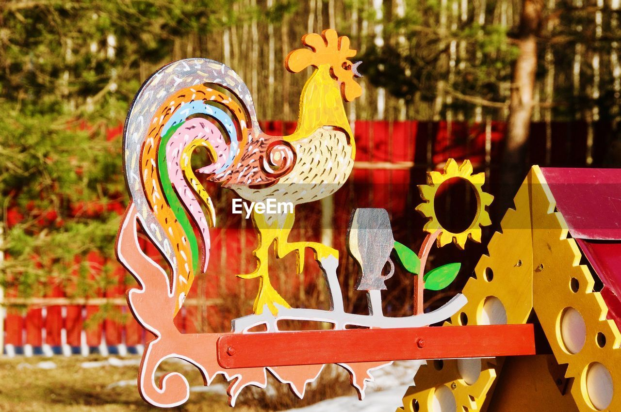representation, art and craft, focus on foreground, animal representation, creativity, multi colored, no people, day, yellow, nature, celebration, craft, outdoors, close-up, animal, tree, decoration, event, animal themes, festival